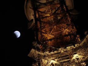 A partial lunar eclipse seen from behind the Tokyo tower, Japan
