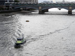 A police boat heads along the River Thames towards London Bridge