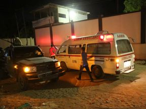 A man walks past an ambulance and armed security forces at the scene of an attack outside an hotel in Mogadishu, Somalia June 14, 2017