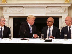 Trump (2nd L) welcomes (L-R) Apple CEO Tim Cook, Microsoft CEO Satya Nadella and Amazon CEO Jeff Bezos