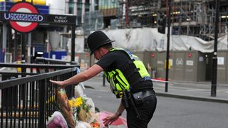A police officer lays flowers passed to him by members of the public on London Bridge