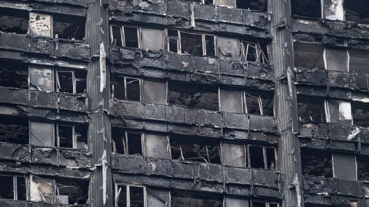 The remains of Grenfell Tower are seen from a neighbouring tower block