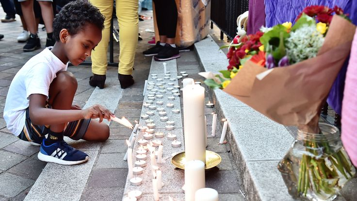 A boy lights a candle at a vigil for the Grenfell Tower victims