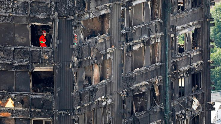Members of the emergency services work on the middle floors of the charred remains of Grenfell Tower