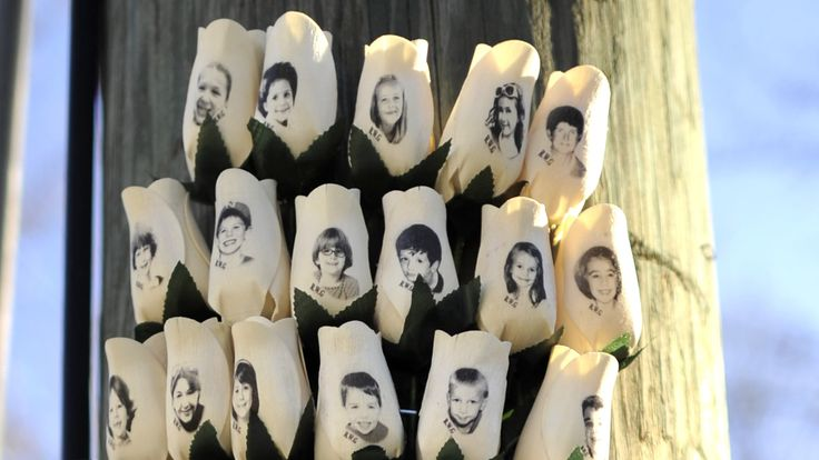 Roses with the faces of the Sandy Hook Elementry students and adults killed are seen on a pole in Newtown, Connecticut on January 3, 2013