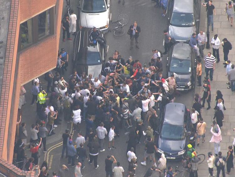 Dozens of people appeared to push and shove each other outside the town hall