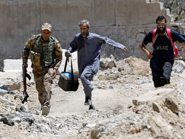 An Iraqi soldier and civilians run to avoid snipers of the Islamic State militants