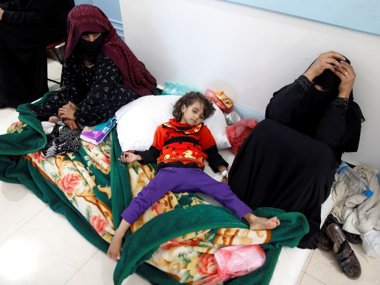 A mother holds her heads in her hands as she sits next to a young girl with cholera in Sanaa, Yemen