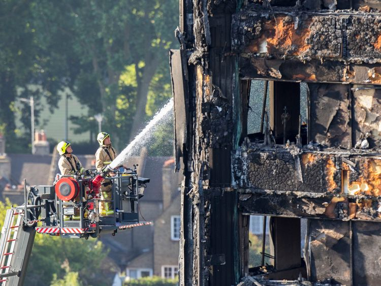 Firefighters continue to dampen down the tower block following the deadly blaze