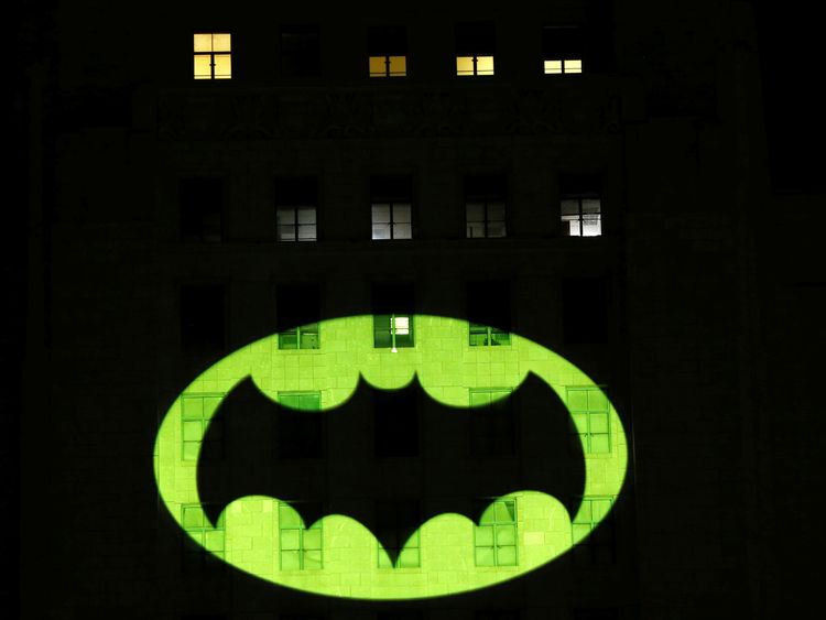 People watch as a bat-signal is projected on City Hall in honour of late actor Adam West in Los Angeles, California