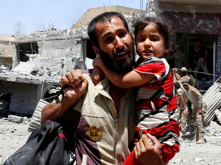 A man displaced by fighting between Iraqi forces and Islamic State militants carries his daughter in Mosul's al-Zanjili's district, Iraq June 7, 2017