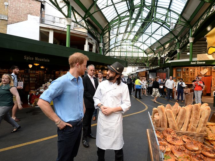 Prince Harry speaks to Matthew from the Bread Ahead stall during a visit to Borough Market, which has officially opened following the London Bridge attack