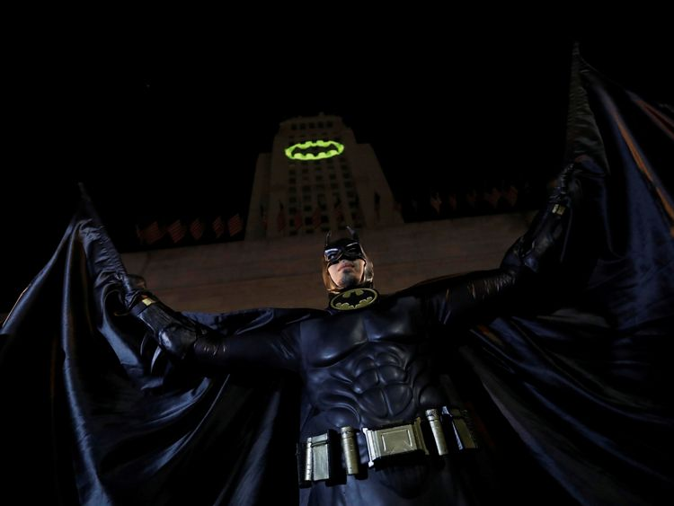 A person wearing a Batman costume poses for photos as a bat-signal is projected on City Hall
