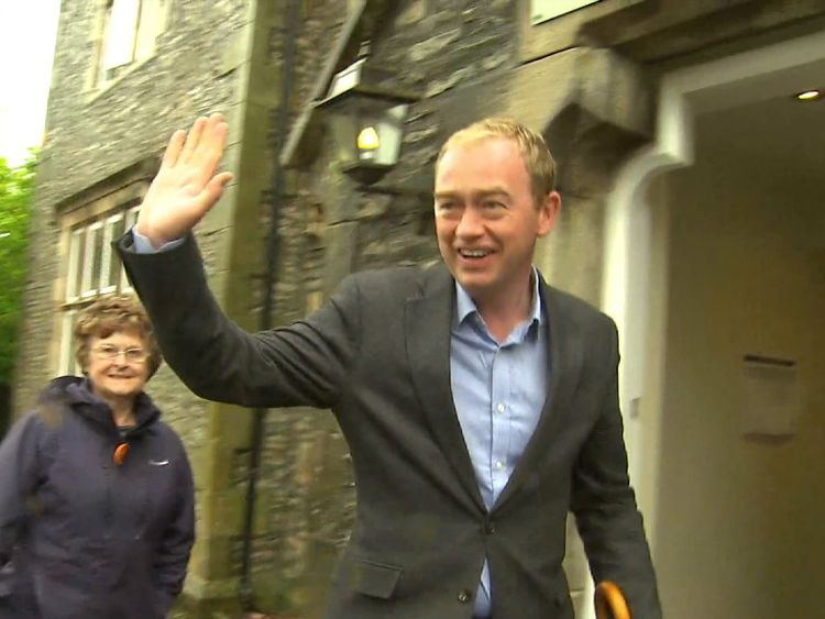 Tim Farron waves to the cameras before casting his vote