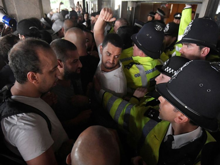 Police confront protesters outside the town hall