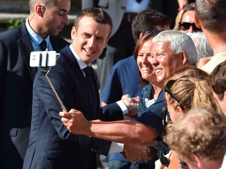 French President Emmanuel Macron (L) poses for a selfie picture with a supporter as he leaves his house to vote in Le Touquet, northern France, during the second round of the French parliamentary elections (elections legislatives in French), on June 18, 2017. / AFP PHOTO / Philippe HUGUEN (Photo credit should read PHILIPPE HUGUEN/AFP/Getty Images)