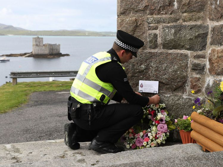An officer from Police of Scotland lays flowers on behalf of Manchester Police