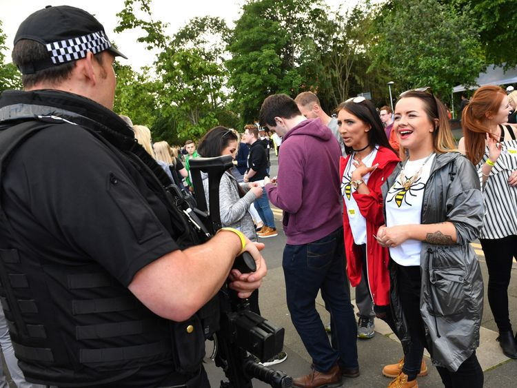 Two women share a laugh with an armed police officer