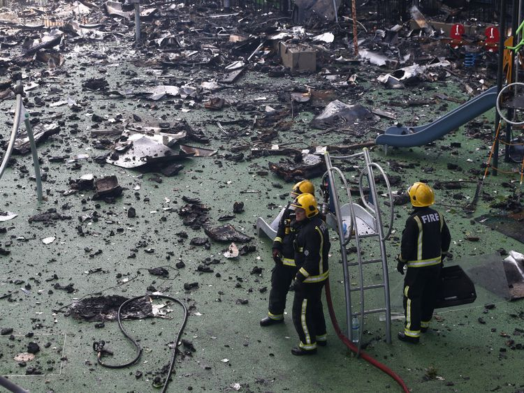 Firefighters stand amid debris in a childrens playground near a tower block severly damaged by a serious fire, in north Kensington, West London