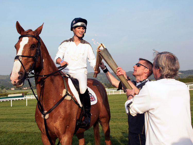 Olympic Torchbearer Zara Phillips carries the Olympic Flame whilst riding her horse Toytown at Cheltenham Racecourse on May 23, 2012