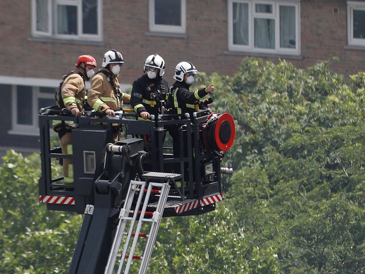 Firefighters use a hydraulic lift to inspect the tower block