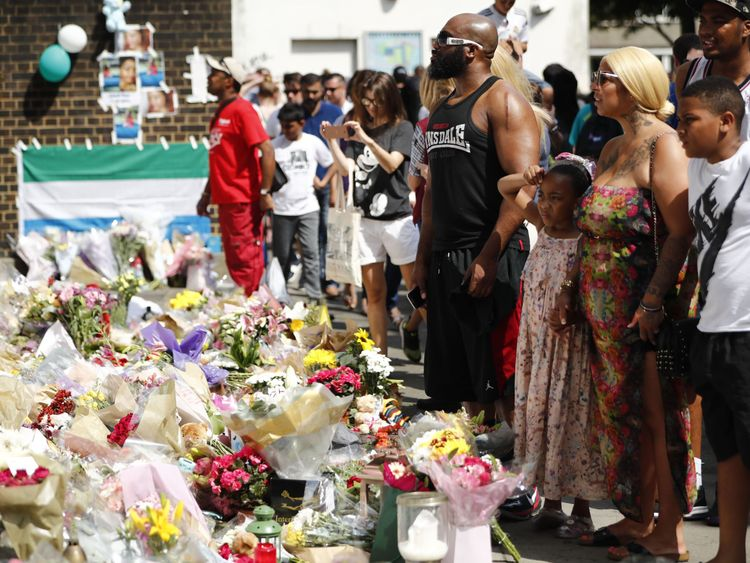 People gather in front of memorial tributes to the victims and the missing from Grenfell Tower