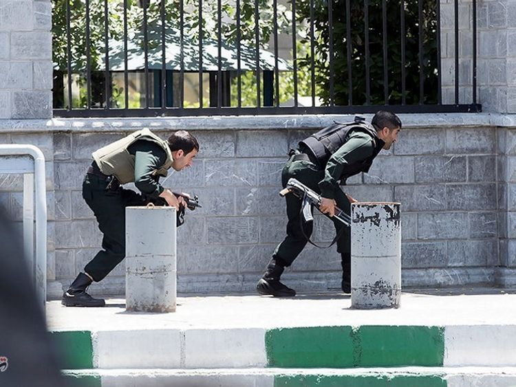 Members of Iranian forces take cover during an attack on the Iranian parliament in central Tehran