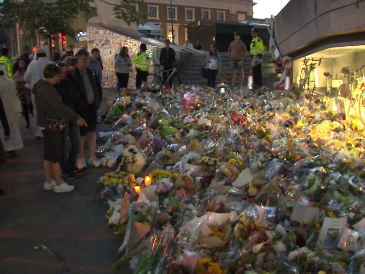 People look at the flowers a week on from the attack that killed eight people
