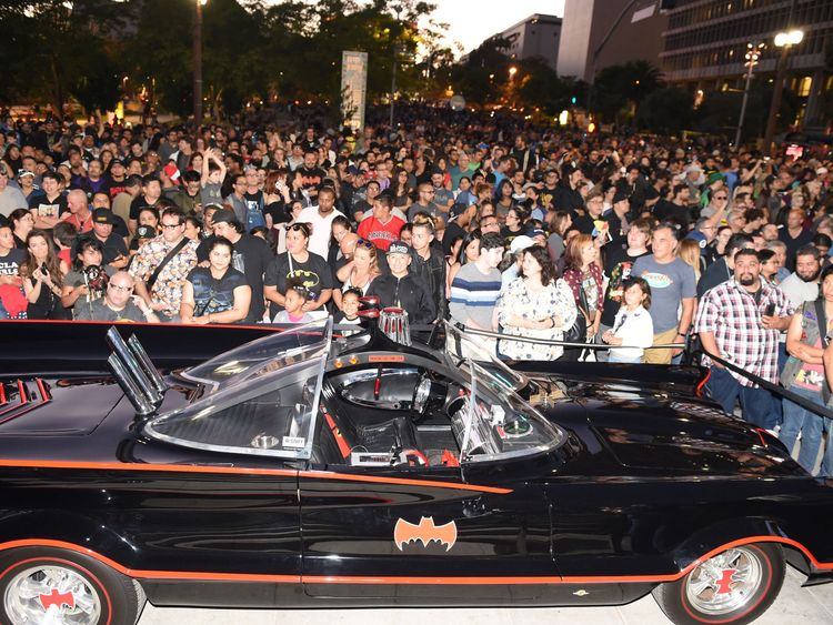 Fans gather around a Batmobile before a tribute to Batman star Adam West