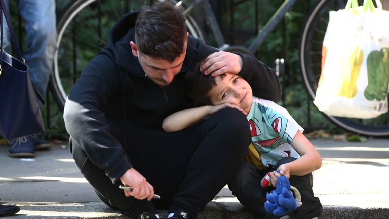 A man comforts a boy near the Grenfell Tower block fire