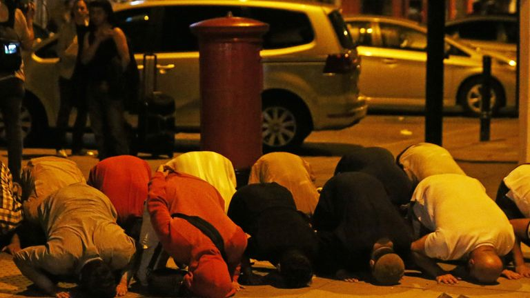 Men pray after a van collides with pedestrians near a mosque in the Finsbury Park area