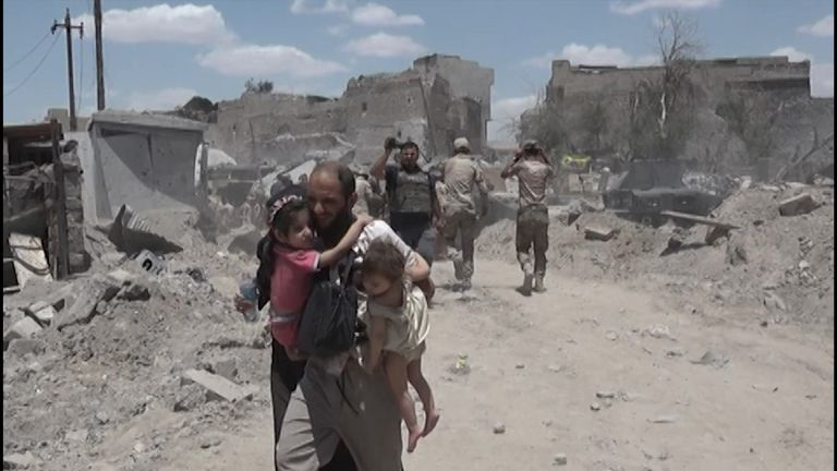 Man carrying children on rubble road.