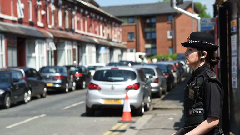 A Police officer stands on duty on Banff Road in Rusholme, Manchester