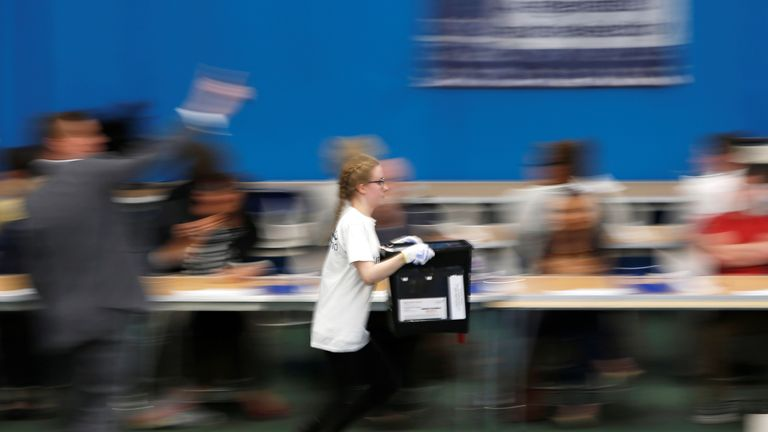 A count worker in Sunderland rushes in with a ballot box as her team aim to be the first to declare