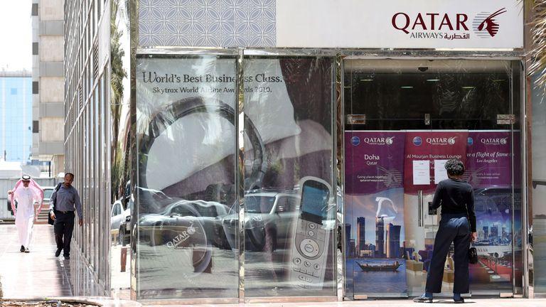 A man stands outside a closed Qatar Airways branch in Saudi Arabia's capital, Riyadh