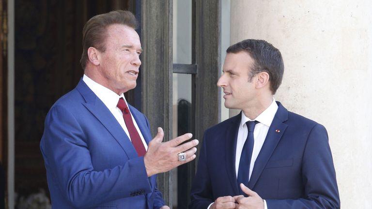 Emmanuel Macron shakes hands with Arnold Schwarzenegger