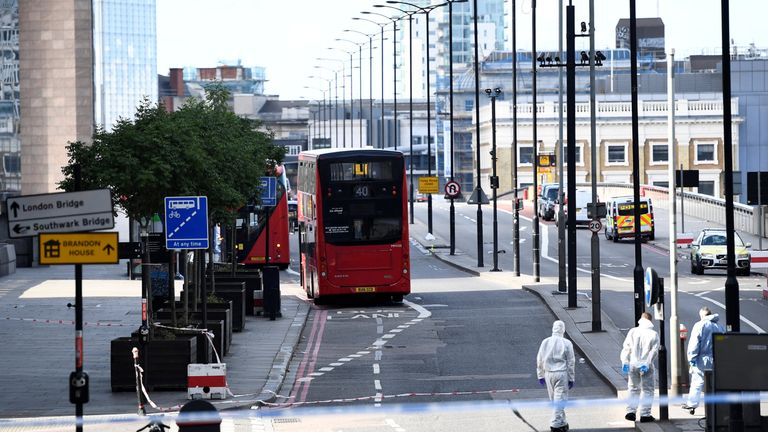 Police forensics investigators work on London Bridge near abandoned buses