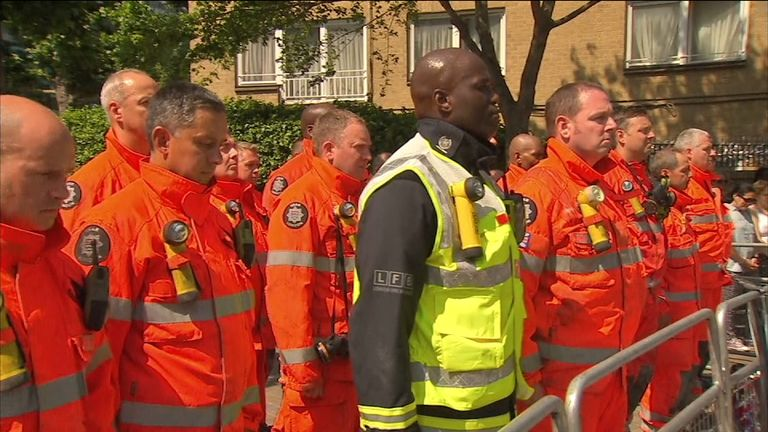 Emergency workers observe a moment of silence at the Grenfell site