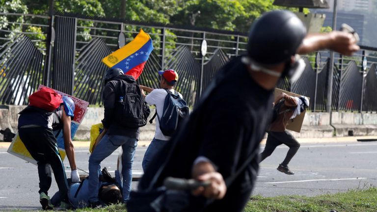 A member of the riot security forces points a gun through the fence at an opposition supporter