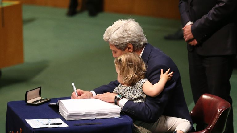U.S. Secretary of State John Kerry signs the Paris Agreement For Climate Change while holding his granddaughter Isabelle Dobbs Higginson during the Paris Agreement For Climate Change Signing at United Nations on April 22, 2016 in New York City