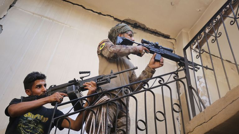 Members of the Iraqi Counter-Terrorism Service ascend a staircase as they clear a building