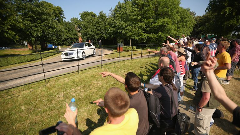 Demonstrators gesture from the protester encampment as vehicles arrive at The Grove hotel, which is hosting the annual Bilderberg conference on June 6, 2013 in Watford, England.