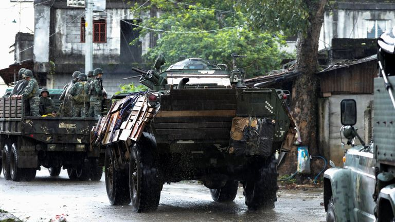 Military vehicles drive along a street while government forces continue their assault