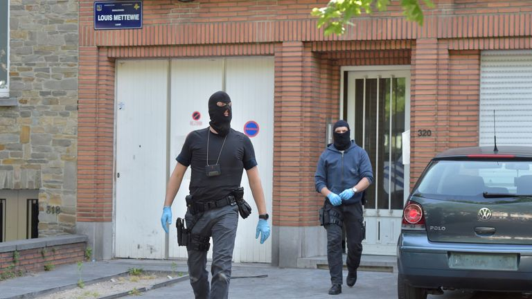 Masked police leave a building during a raid in Molenbeek