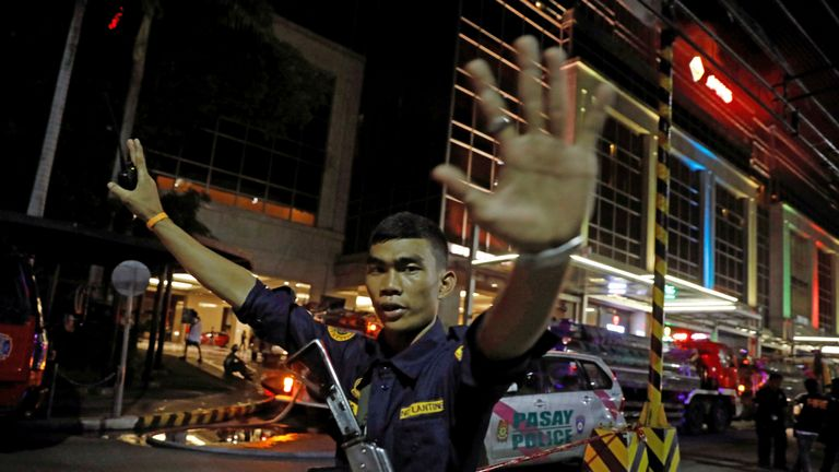 A security guard stops photographers from entering the vicinity of Resorts World Manila