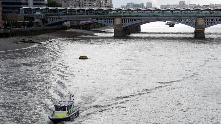 A police boat heads along the River Thames towards London Bridge