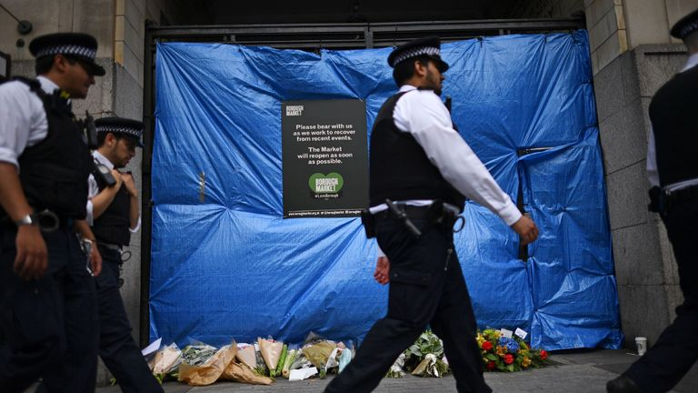 Police officers walk past floral tributes at a covered entrance to Borough Market in London on June 11, 2017, following the June 3 terror attack that targeted members of the public on London Bridge and Borough Market
