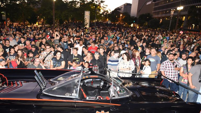 Fans gather around a Batmobile before a tribute to Batman star Adam West