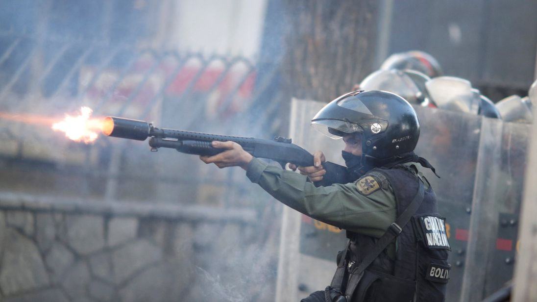 A riot security force member fires his weapon
