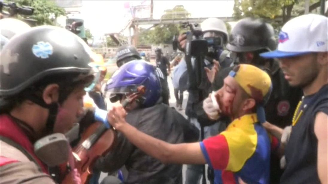 Venezuela violinist being helped by paramedics after march